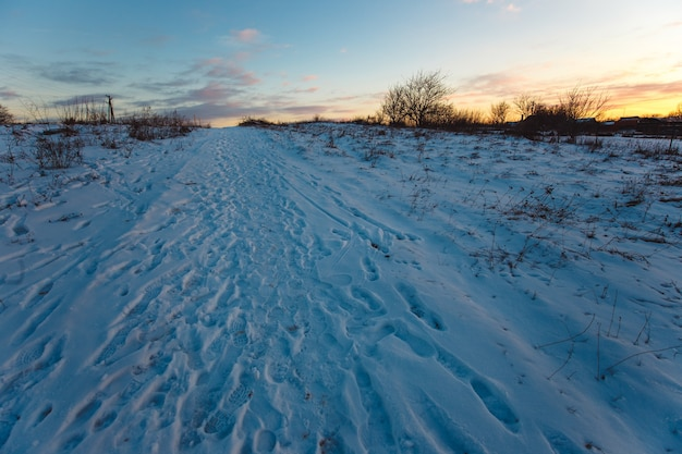Campagna di sentiero innevato al tramonto.