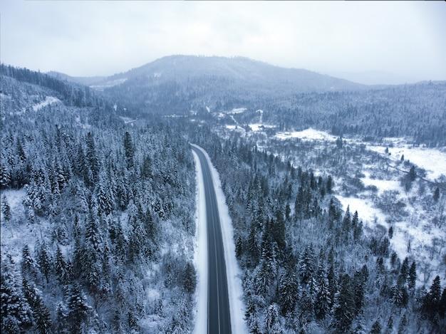 Strada innevata attraverso un paesaggio montano boscoso in inverno.