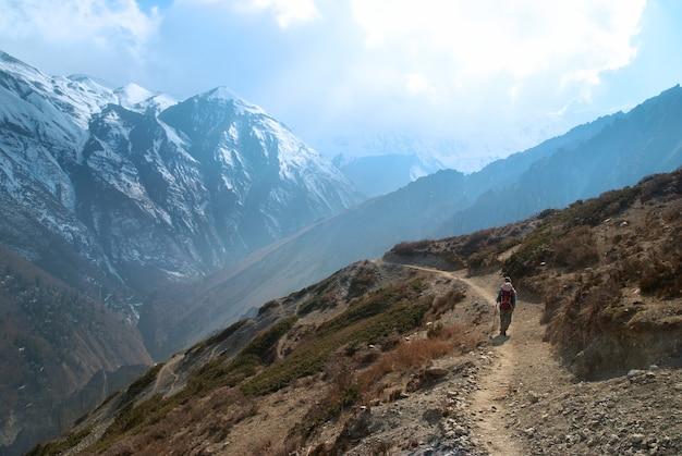 Montagne tibetane innevate con escursionismo uomo