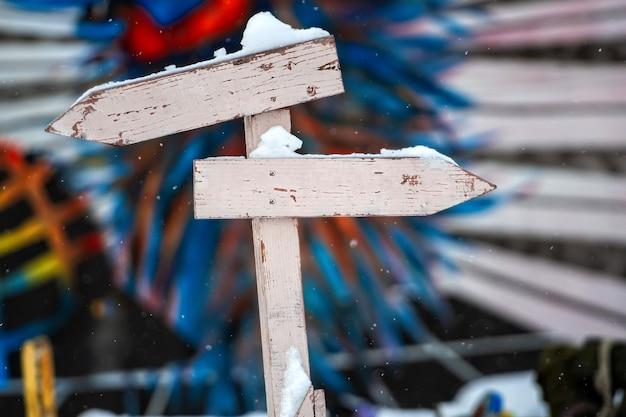 Cartello in legno innevato con due frecce nlank su una superficie sfocata colorata