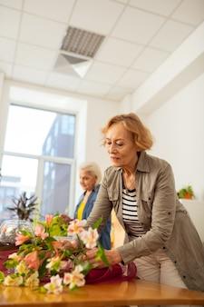 Così bello. gioiosa donna anziana che sorride mentre guarda il bellissimo bouquet