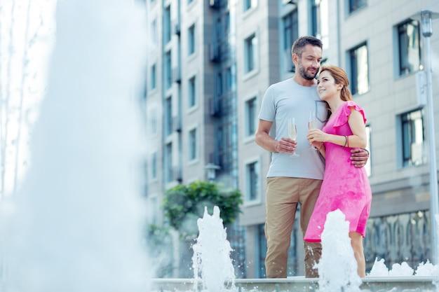 Così bello. bella coppia allegra guardando la fontana tenendo i bicchieri di champagne