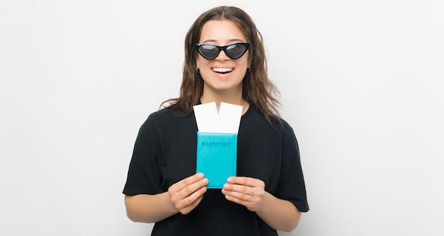 Fantastico, ho due biglietti di viaggio. la giovane donna sta tenendo il suo passaporto.