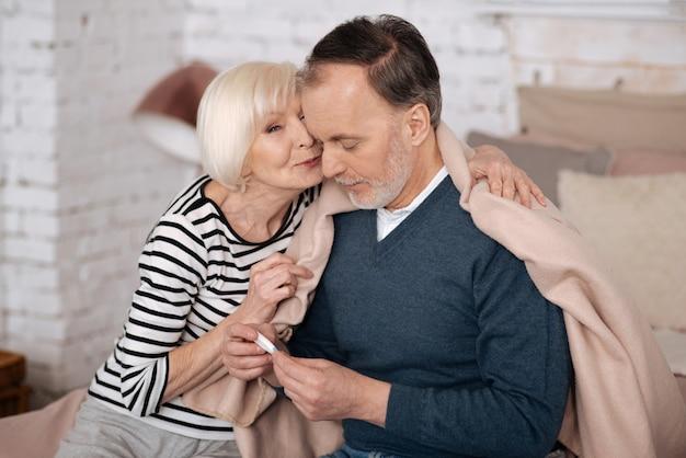 Così carino. piacevole donna senior sta baciando il marito malato seduto coperto di coperta vicino a lei.