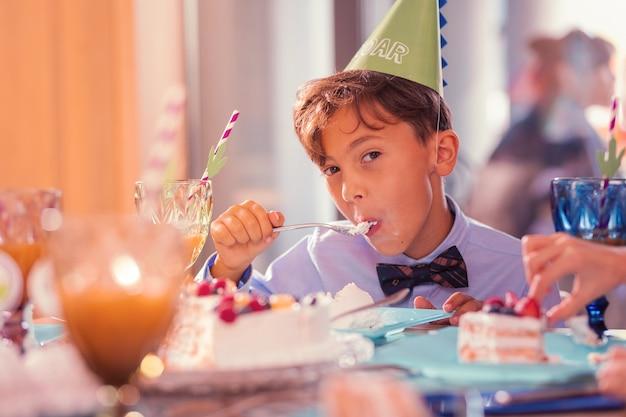 Così delizioso. ragazzo concentrato che indossa un cappello da festa e mangia minuziosamente gustosa torta mentre è alla festa