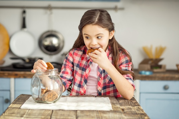 Così delizioso. bambina dai capelli scuri piuttosto gioiosa seduta al tavolo e mangiare un biscotto e prendere un altro po '