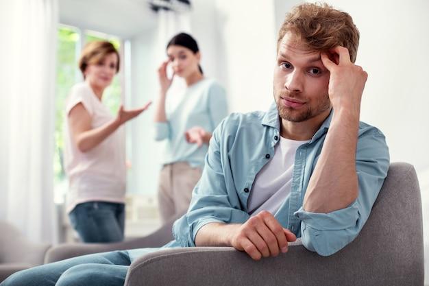 Così depresso. uomo barbuto infelice che tiene la sua fronte mentre pensa ai suoi problemi familiari