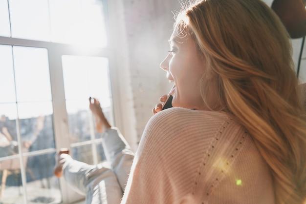 È così bello sentirti! vista posteriore di una bellissima giovane donna che parla sul suo smartphone e sorride mentre è seduta vicino alla finestra di casa