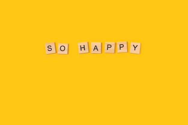 Così felice di scrivere con blocchi di lettere in legno su uno sfondo giallo