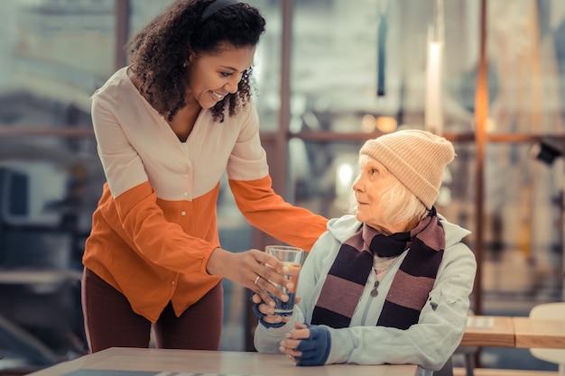 Così utile. felice giovane donna sorridente mentre porta un bicchiere d'acqua