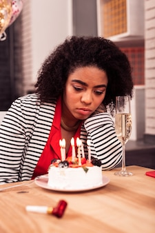 Così solo. cupa donna infelice guardando la torta pur avendo una triste festa di compleanno