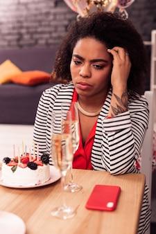 Così solo. cupa giovane donna in attesa di una chiamata mentre festeggia il suo compleanno da solo