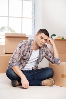 Tanto lavoro avanti. giovane depresso seduto sul pavimento e appoggiato alla scatola di cartone mentre più scatole di cartone posate sullo sfondo
