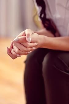 Così nervoso. messa a fuoco selettiva delle mani femminili tenute insieme pur essendo preoccupato