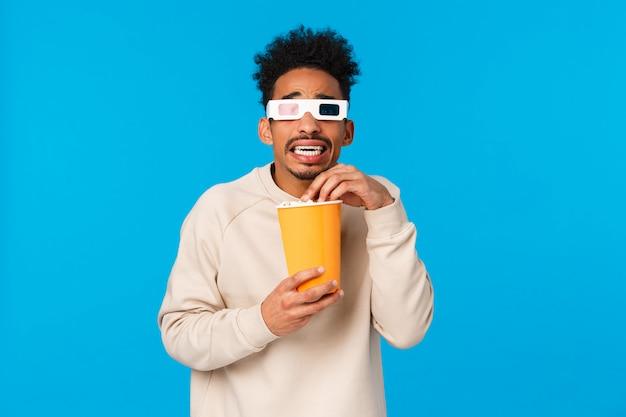 Così spaventoso. ragazzo hipster afroamericano tremante e terrorizzato guardando film horror, scena spaventosa in occhiali 3d film, tenendo la scatola di carta e mangiando popcron, in piedi teso, parete blu