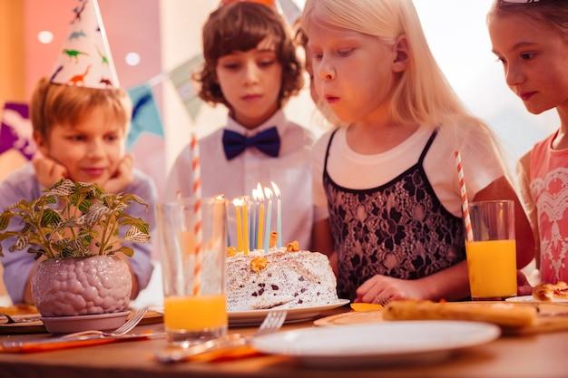 Così forte. sagoma di bambini che stanno vicino al loro amico e guardando la torta