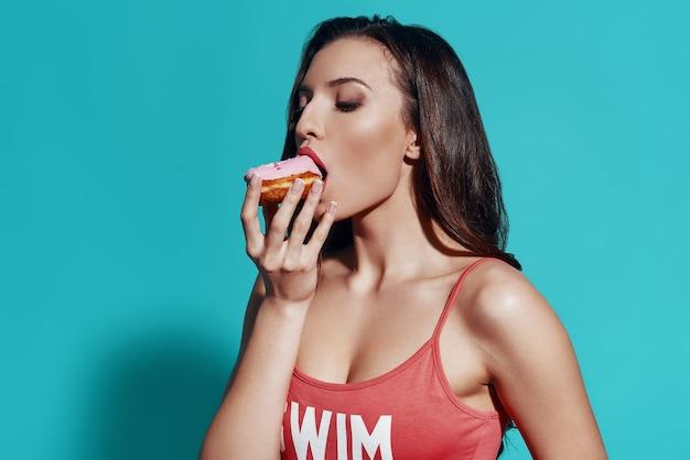 Così saporito! bella giovane donna in costume da bagno che mangia ciambella mentre sta in piedi su sfondo blu