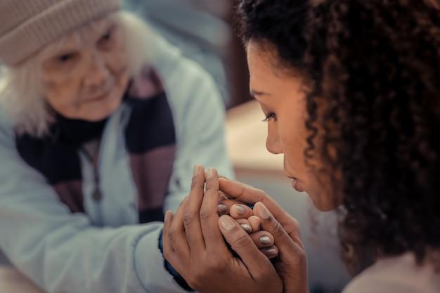 Così grato. donna senzatetto triste guardando il suo aiutante pur essendo grato a lei