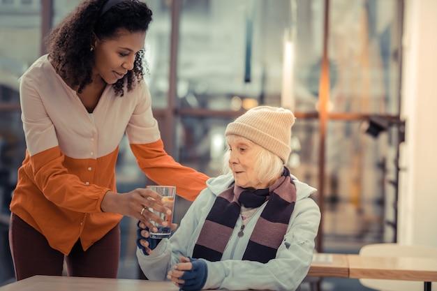 Così assetato. bella donna anziana che prende un bicchiere con acqua pur essendo molto assetata