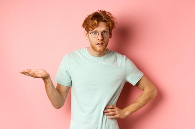 E allora. uomo rosso confuso alzando la mano e scrollando le spalle, guardando perplesso, non capisco qualcosa, in piedi su sfondo rosa.