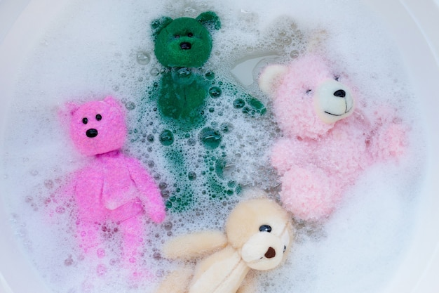 Immergere gli orsetti giocattolo nella dissoluzione dell'acqua detergente per bucato prima del lavaggio. concetto di lavanderia, vista dall'alto