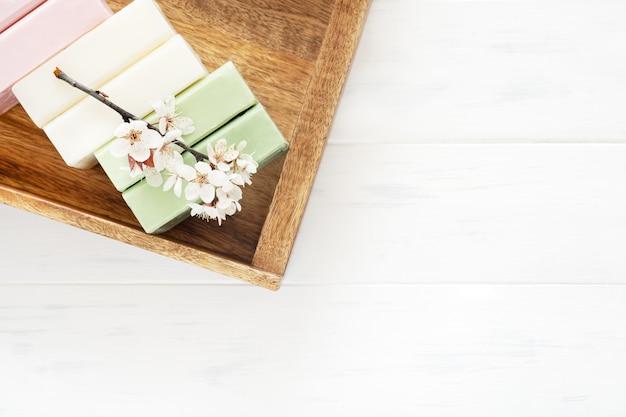 Sfondo di sapone. sapone naturale aromatico con fiori di sakura su fondo bianco in legno, vista dall'alto
