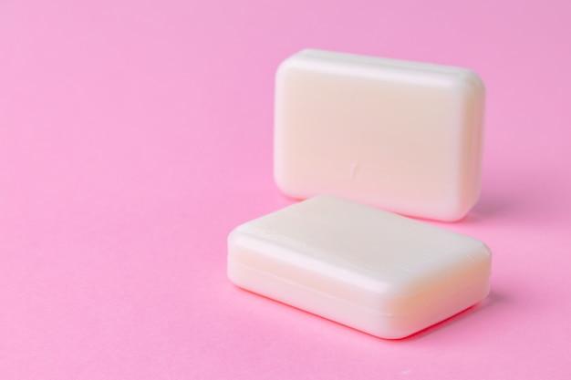 Barra del sapone isolata su fondo rosa. avvicinamento.