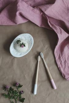 Saponetta o shampoo solido su un portasapone spazzolino da denti in bambù e asciugamano vista dall'alto con accesso copyspace...