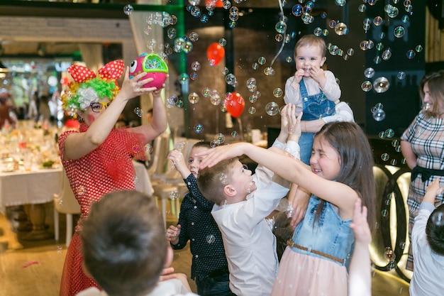 Le bolle di sapone mostrano i pagliacci alla festa dei bambini