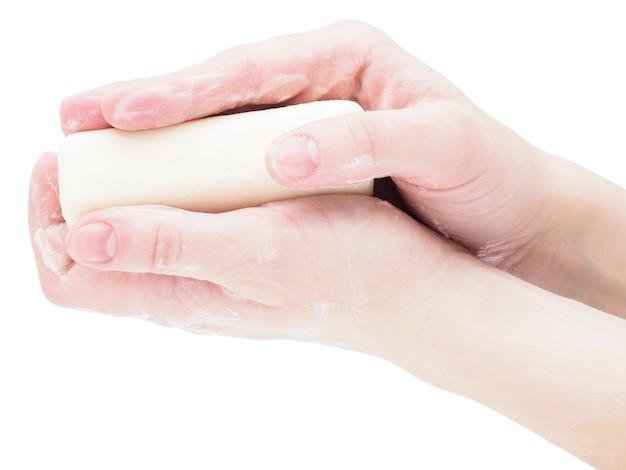 Mani di sapone che tengono una saponetta, close-up, isolare su uno sfondo bianco.