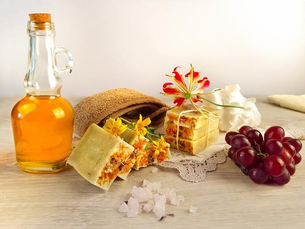 Sapone a base di erbe medicinali e medicinali e fiori olio di semi d'uva sale rosa dal tibet fiori e un asciugamano su un tavolo di legno bianco