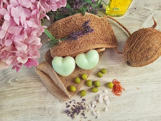 Sapone per cure termali due saponette a forma di cuore fatte di oliva e olio di cocco zafferano lavanda sale tibetano e tutti gli ingredienti giacciono su una luffa naturale su un tavolo vintage in quercia bianca