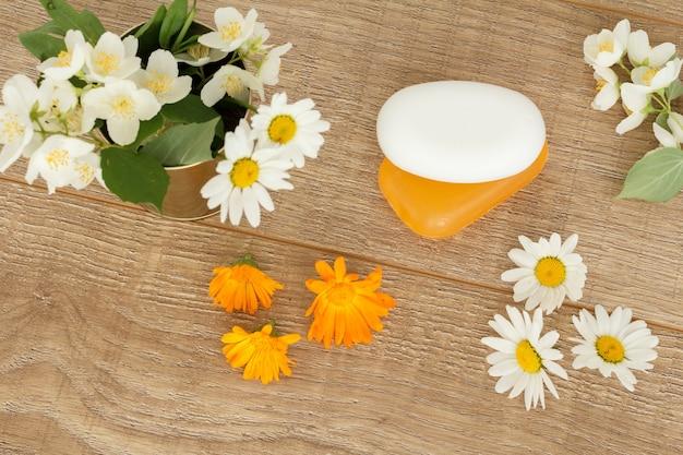 Sapone con fiori di camomilla bianca e fiori di calendula gialla sulla scrivania in legno. vista dall'alto.