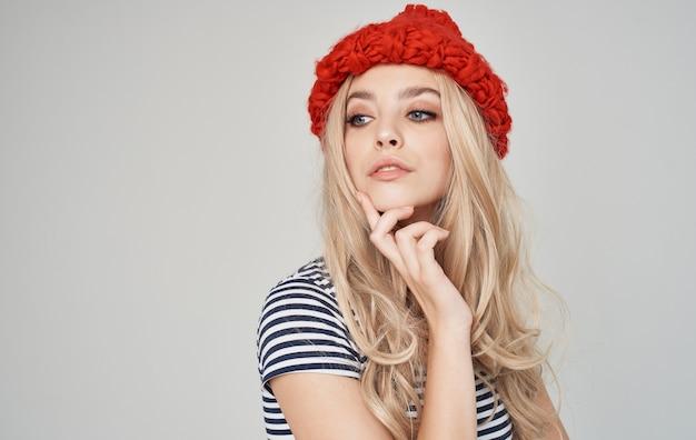 Sapone donna con un cappello rosso in una maglietta a righe su una bionda di sfondo grigio
