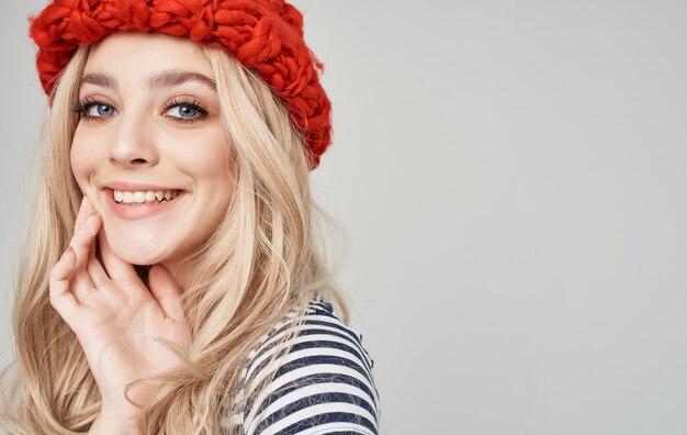 Sapone donna con un cappello rosso in una maglietta a righe su una bionda grigia.