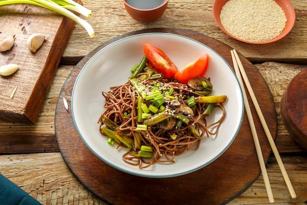 Soba con funghi, fagiolini e semi di sesamo in un piatto su un supporto su un tavolo di legno accanto a bacchette e salsa di soia e aglio su supporti. foto orizzontale