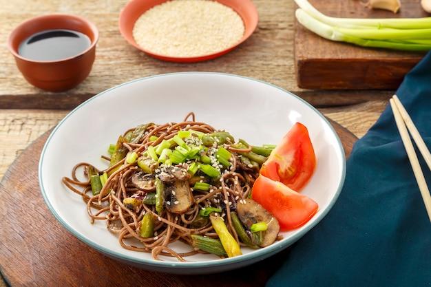 Soba con funghi, fagiolini e semi di sesamo in un piatto su un supporto su un tavolo di legno accanto a bastoncini e salsa di soia e semi di sesamo. foto orizzontale.