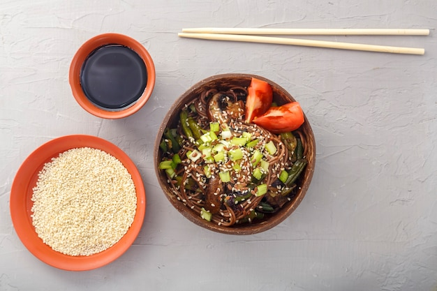 Soba con funghi e semi di sesamo in una ciotola di gusci di cocco su uno sfondo di cemento accanto a semi di sesamo e salsa di soia e bastoncini. foto orizzontale