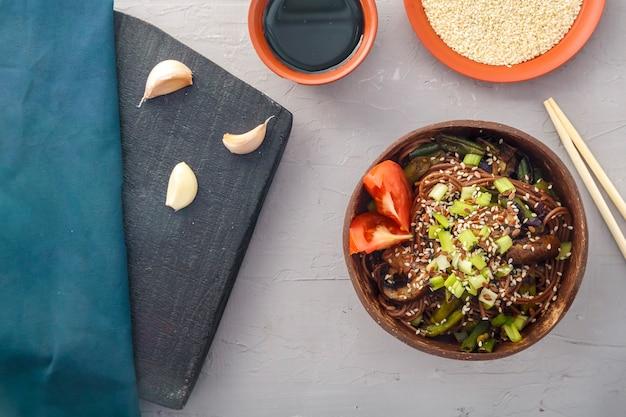 Soba con funghi e semi di sesamo in un piatto di cocco skrlup su uno sfondo grigio cemento accanto all'aglio e salsa di soia. foto orizzontale