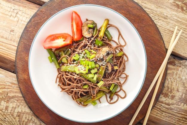 Soba con funghi e semi di sesamo in un piatto su un supporto su un tavolo di legno accanto alle bacchette. foto orizzontale.