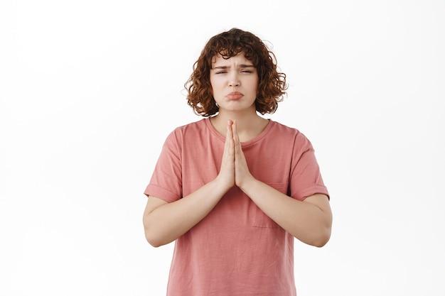 Singhiozzando ragazza carina e sciocca che chiede aiuto, scuse, implorando aiuto o favore, ha bisogno di qualcosa, supplica, in piedi su bianco in t-shirt