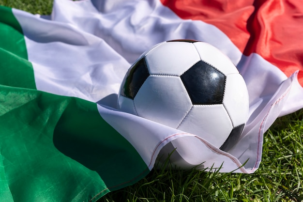Pallone da calcio sullo sfondo della bandiera italiana che fluttua nel vento sull'erba verde campioni europei green