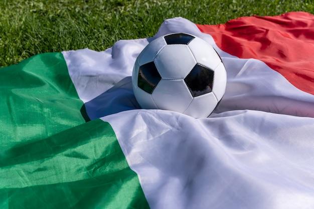 Pallone da calcio sullo sfondo della bandiera italiana che fluttua nel vento sull'erba verde campioni europei