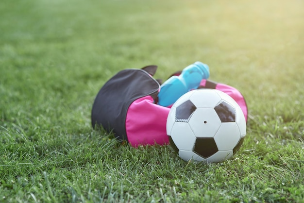 Pallone da calcio bottiglia d'acqua e borsa sportiva su erba verde
