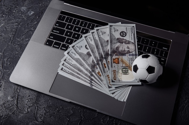 Pallone da calcio e banconote in dollari su una tastiera. sport, gioco d'azzardo, concetto di scommessa.
