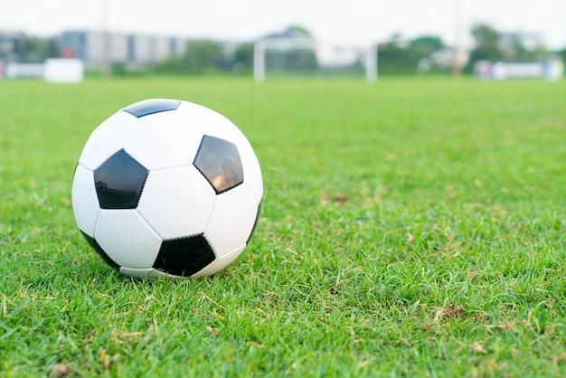 Pallone da calcio sui precedenti del campo di calcio con lo spazio della copia