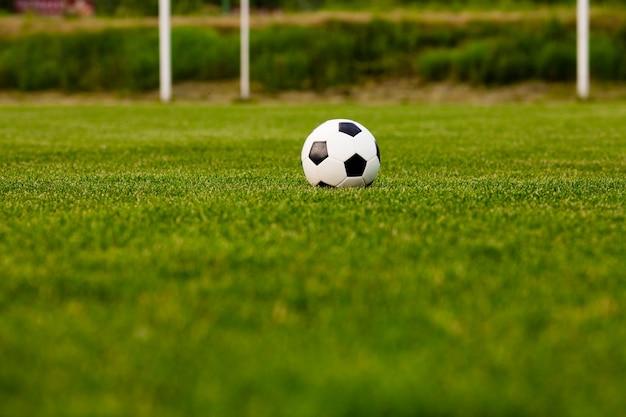 Pallone da calcio su un primo piano dell'erba verde. concetto - passione per il calcio