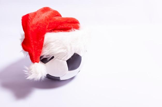 Pallone da calcio in un cappello di babbo natale su uno sfondo bianco