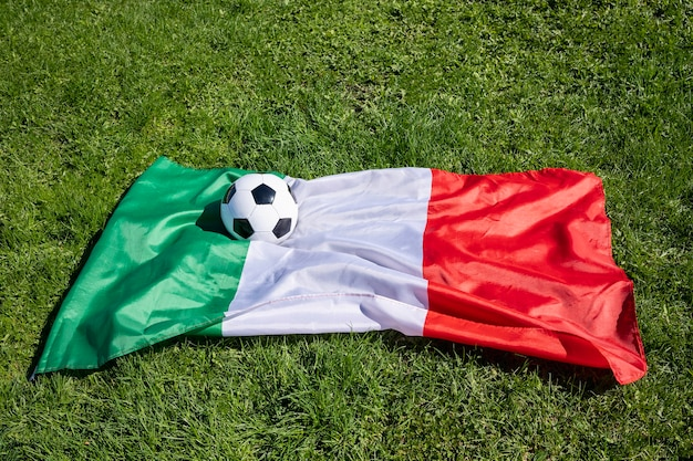 Pallone da calcio sulla superficie della bandiera italiana sulla partita di apertura del campionato europeo di erba verde di