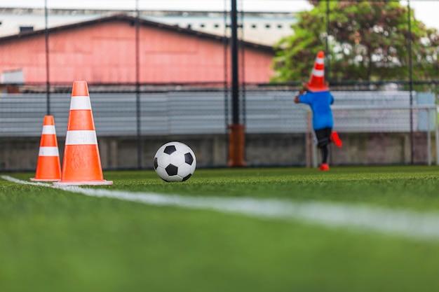 Cono di tattiche del pallone da calcio sul campo in erba con sfondo di allenamento formazione dei bambini nel calcio